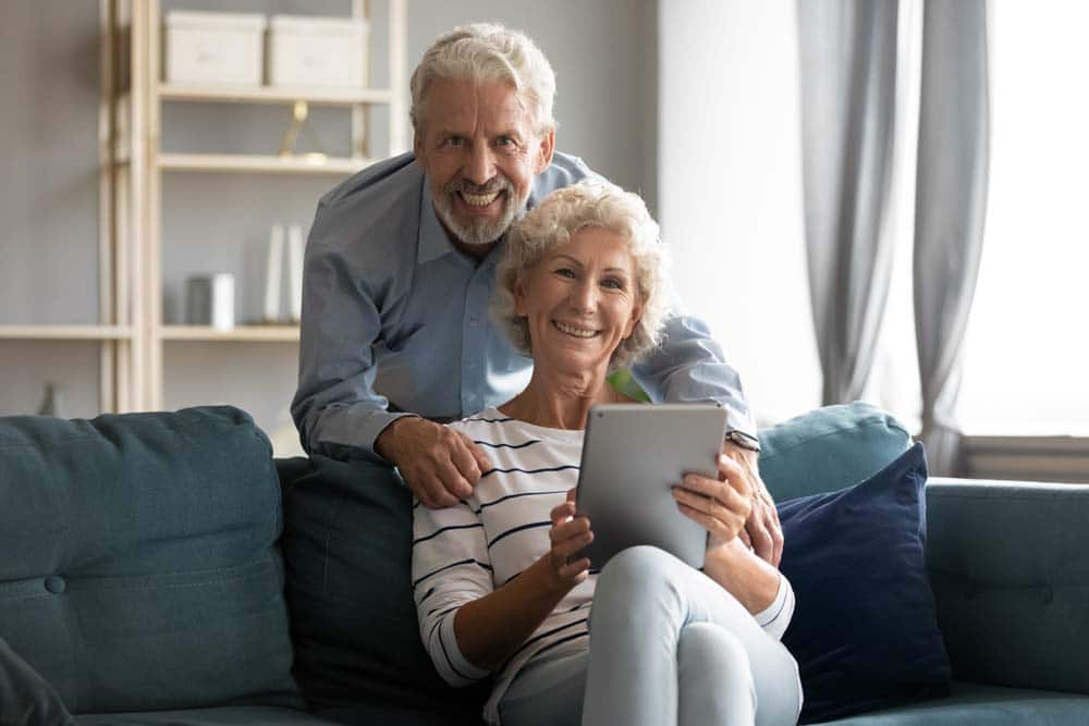 Older caucasian couple with sliver hair on the couch smiling searching properties on iPad